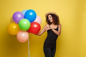 Celebration Concept - Close up Portrait happy young beautiful african woman in black t-shirt smiling with colorful party balloon. Yellow Pastel studio Background