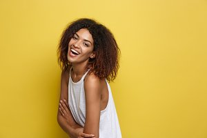 Headshot portrait of beautiful attractive African American woman posting crossed arms with happy smiling. Yellow studio background. Copy Space