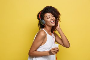 Lifestyle Concept - Portrait of beautiful African American woman joyful listening to music on mobile phone. Yellow pastel studio background. Copy Space