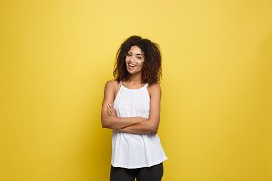 Portrait of beautiful attractive African American woman posting crossed arms with happy smiling. Yellow studio background. Copy Space.