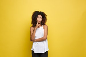Beautiful attractive African American woman with curly afro hair thinking of something. Yellow studio background. Copy Space.