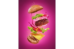 The hamburger with flying ingredients on lilac background
