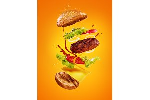 The hamburger with flying ingredients on orange background