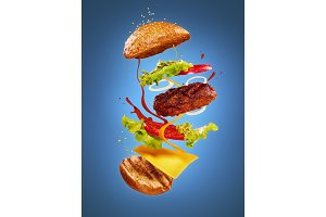 The hamburger with flying ingredients on blue background