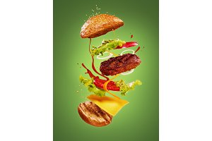 The hamburger with flying ingredients on green background