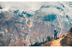 Woman with backpack on the path and mountains