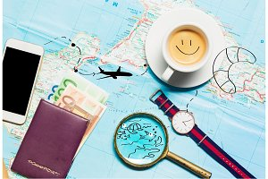 Preparation for travel concept - map, magnifying glass, cup of coffee, notepad, phone