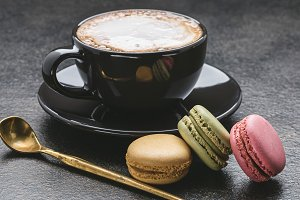 Cup of cappuccino, macaroons.