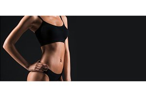 The torso of attractive female body builder on black background.