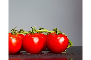 The fresh cherry tomatos on gray background