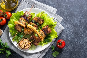 Grilled shish kebab or shashlik on black stone table.