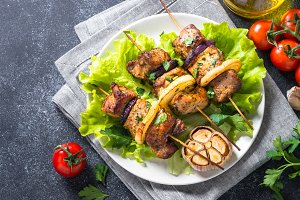 Grilled shish kebab or shashlik on black stone table top view.