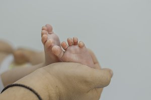 father's hand holding newborn feet