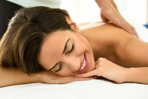 Smiling girl receiving spa massage
