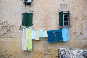 multi-colored linen is dried outside the window of an old house