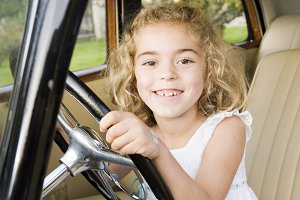 Little girl sitting in an old car