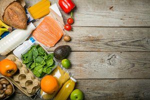 Grocery shopping concept. Balanced diet concept. Fresh foods with shopping bag on rustic wood background