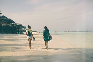 Two girlfriends walking ocean coast