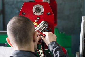 Electrician works with energy panel and machinery equipment on plant