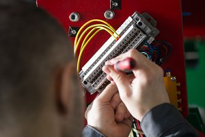 Hands of electrician engineer screwing and testing equipment in fuse box