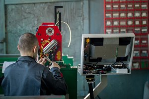 Electrician with scissor is installing energy system on machinery industry