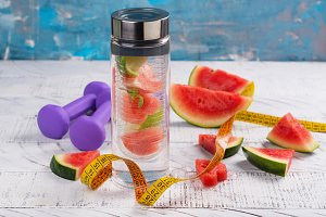 Homemade watermelon detox infused water, dumbbells and measuring tape on wooden background