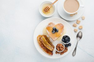 A stack of delicious pancakes with honey, coffee and blueberries on a light blue background. Great Breakfast for Valentine's day. Top view with copy space
