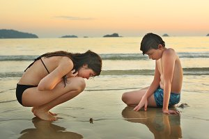 teenager siblings on seaside beach looking for shell crab and corall pieces