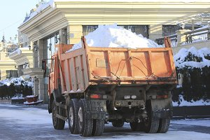 Truck carrying the snow on the street in winter