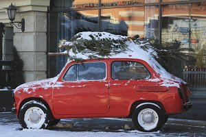 Snow-covered retro car on the street, Christmas tree on the roof