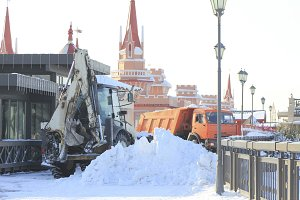 Clearing snow from the road with bulldozer and truck in the city