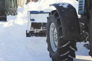 Clearing snow from the road with bulldozer in the city in winter, focus on blade and wheel