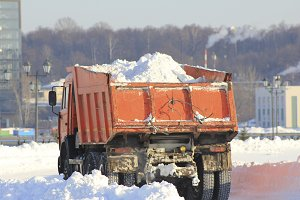 Truck carrying the snow on the street in winter, cleaning of streets