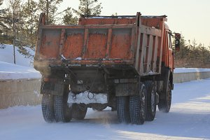 Dirty truck carrying the snow on the street in winter