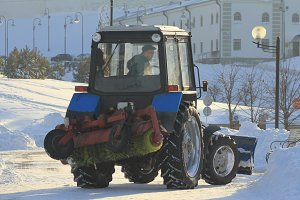 Clearing snow from the road with tractor in the city in winter