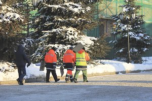 Group of workers with shovels in overalls walking on winter snow-covered street in the city
