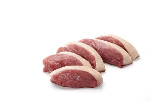 Raw duck breast pieces on white