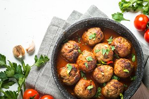 Meat balls in tomato sauce in a frying pan top view.