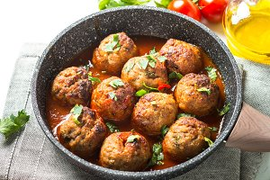 Meat balls in tomato sauce in a frying pan.