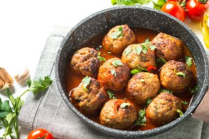 Meatballs in tomato sauce in a frying pan.