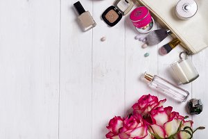 Women cosmetics and fashion items on white wooden background with copy space