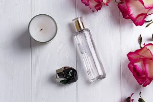 Perfume bottle, candle and pink rose