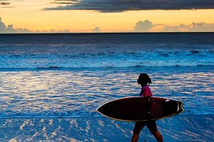 Surfgirl walking on the beach