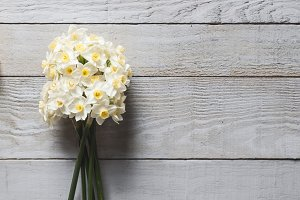White narcissus flowers on wood