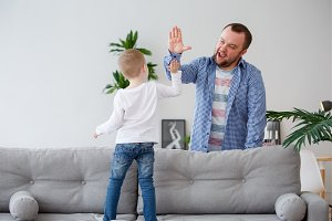 Family photo of young son standing on sofa making handshake with dad