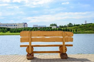 old wooden bench by the lake on a summer day