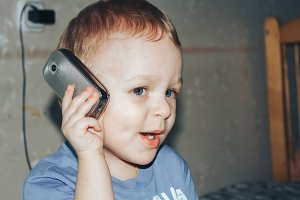 little boy is calling on the phone at home