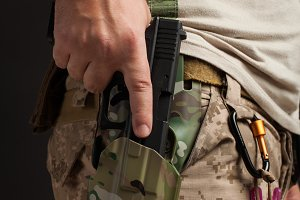 Close-up of a gun that properly holds a man in a military desert uniform and body armor on a black background in the Studio. The man grabs a gun out of the holster for self-defense
