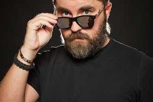 A handsome, strong man with a stylish hairstyle and beard dresses sunglasses in the Studio on a black background
