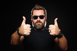 A handsome, strong man with a stylish hairstyle and beard shows two thumbs up in the Studio on a black background. With copy space for your text